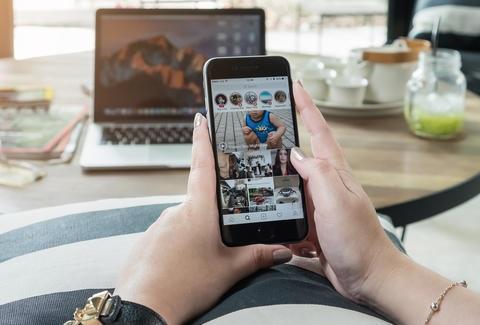 peron holding phone using instagram app